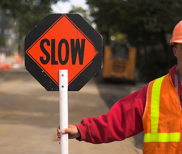 """Flagger directing traffic, holding """"Slow"""" sign"""